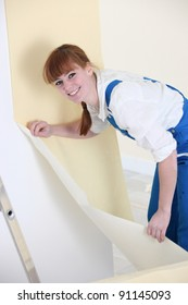Woman hanging wallpaper