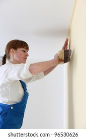 Woman hanging wall-paper