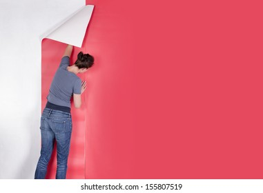 Woman hanging wallpaper. Decorating the wall