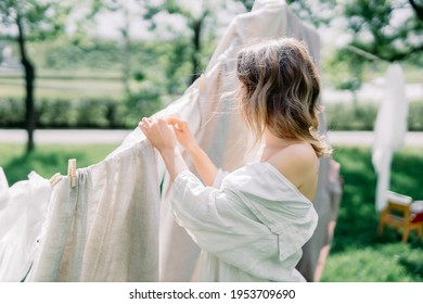 Woman Hanging Up Wet Laundry On Clothesline. The concept of unity girl with nature and the beginning of spring time with flowering trees. sunny day in village