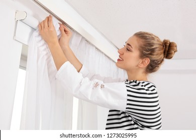 Woman hanging window curtain indoors. Interior decor element