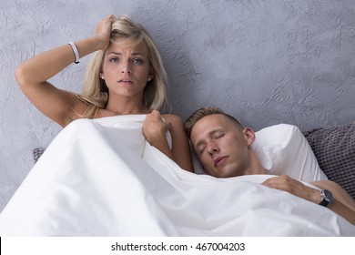 Woman with a hangover lying in a hotel bed with sleeping handsome man