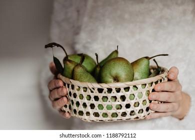 Woman hangs a basket with juicy pears.