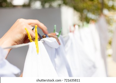 Woman hangs on clothesline some clothes by wood pin / spill during lovely spring / summer time / weather