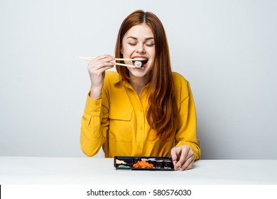 A woman happily eating rolls, light background, the woman behind the desk light