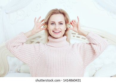 Woman happily smiles, holds Bitcoins in her hands.