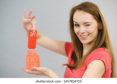 Woman is happy about buying house in affordable price. Female holding small red home model and sale percentage sign. Reduced housing prices. Fall and crisis of real estate market. Low rent