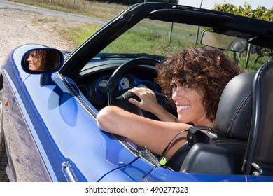Woman happy in blue cabriolet driving on road trip on beautiful sunny summer day.