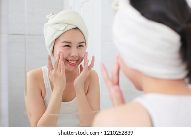 Woman happy cleanses the skin with foam on sink.