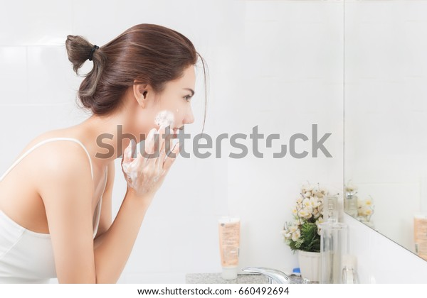 Woman happy cleanses the skin with foam in bathroom.