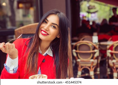 Woman happy. Closeup portrait beautiful smiling toothy girl student looking at you camera holding spoon eating desert in coffee shop background. Multicultural mixt race arabian model Happiness concept