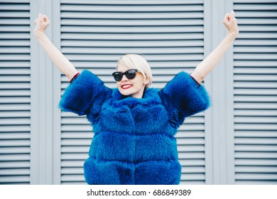 Woman happy concept. Successful woman in fur coat raising hands to sky. Stylish blonde  girl.