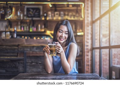 Woman happy drinking a beer in a restaurant.