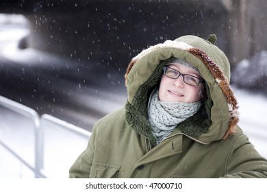 Woman with happy expression posing in warm clothes in snow