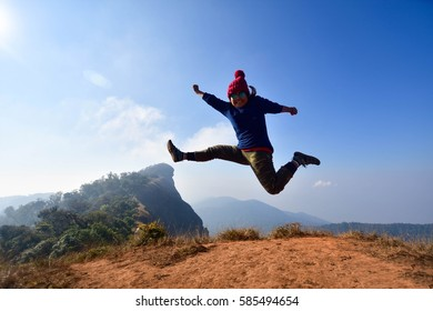 woman happy and jump on top mountain at sunny day. subject is blurred and low key