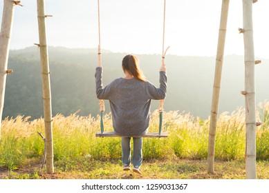 woman happy on swing in sun light.