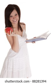 A woman happy reading a book and holding on to a piece of fruit.