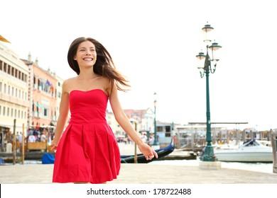 Woman happy running in summer dress, Venice, Italy. Girl smiling laughing joyful having fun by water in Venice. Beautiful multiracial Asian Caucasian young woman cheerful and vivacious.