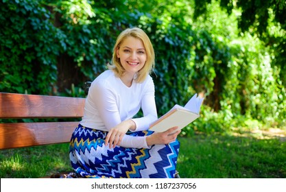 Woman happy smiling blonde take break relaxing in garden reading book. Lady enjoy self imrovement and education. Girl sit bench relaxing with book, green nature background. Improve your knowledge.