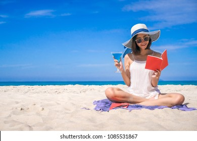 Woman happy smiling and read books on the beach on the beach on a beautiful . Pretty girl asian in casual looking away and smile , laughing. The beach beautiful at bright sky