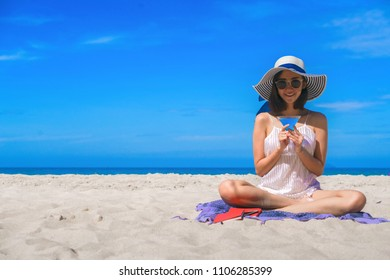 Woman happy smiling read books with cocktail on the beach on the beach on a beautiful . Pretty girl asian in casual looking away and smile , laughing. The beach beautiful at bright sky