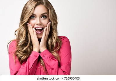 Woman  happy and surprised shouts holds cheeks by hand .Beautiful girl  with curly hair  pointing to looking right . Presenting your product. Expressive facial expressions businesswoman  .