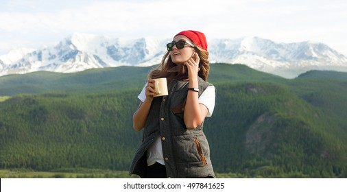 Woman happy traveler with music earphones,hat and cup of hot chocolate on the top of mountains and forest view.True emotions.Soft toned colors,Instagram colors,vsco,cup of hot tea,hiker fitness tracer
