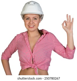 Woman in hard hat making okay gesture, looking at camera, smiling. Isolated on white background