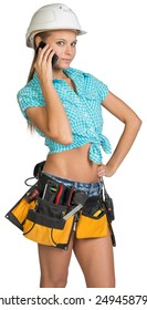Woman in hard hat and tool belt standing akimbo, calling on mobile phone, looking at camera. Isolated on white background