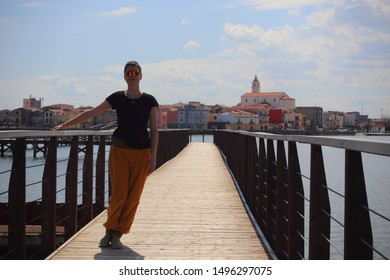 Woman with harem pants standing on Bridge of Lesina, Italy, Tourist lady with sunglasses and short hair enjoying the bridge at the laguna of Lesina on a sunny day in summer