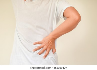 woman has back pain focus on hand holding at pain position with selective focus and white wall background.