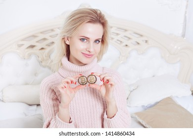 The woman has a bitcoin coin in her hands, with a sweet smile on her face. She is fond of cryptocurrency.