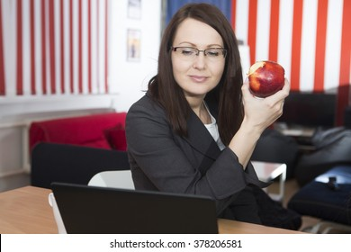 the woman has a bite at work as apple
