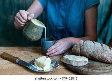 Woman has breakfast adds milk to coffee