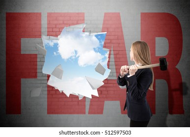 Woman has crashed a white brick wall with sledgehammer and word fear written on it. Sky is seen through the hole. Concept of conquering your fears
