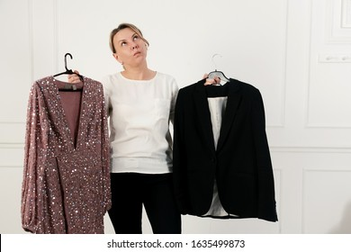 A woman has a difficult choice, not knowing what to wear. Evening dress or business suit. Nothing to wear concept. Woman chooses clothes