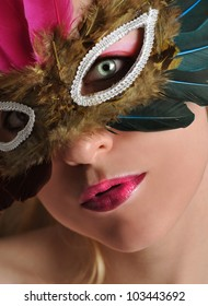 A woman has a feather mask on with bright eyes and lips with makeup. Use it for a Halloween or glamor concept.