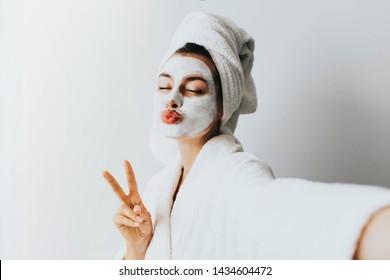 Frau hat Spaß mit einer Gesichtsmaske.Eigenes Portrait von charmantem, stilvollem, hübschem Modell nach dem Baden in Handtuchaufnahmen, die sich auf der Vorderkamera mit Gesichtsmaske für ihr trockenes, geöltes, sinnliches Gesicht umhüllt