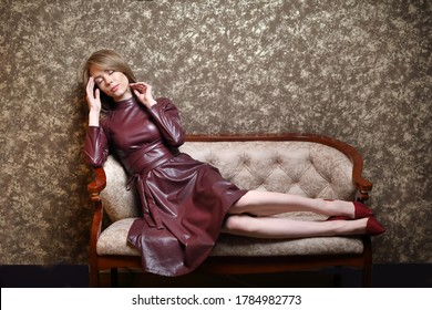 The woman has a headache .  A tired girl in a dress is lying calmly on the sofa, holding her head in her hands. brown mottled background, copy space.