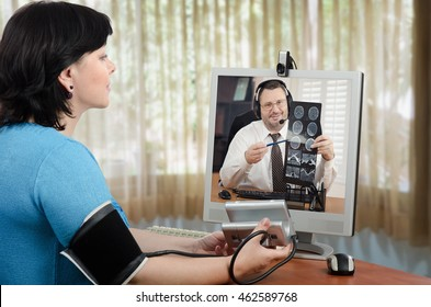 Woman has just measured her blood pressure and shows blood pressure gauges figures to virtual doctor. Male physician in headset is carefully looks it and explains brain x ray picture in the monitor
