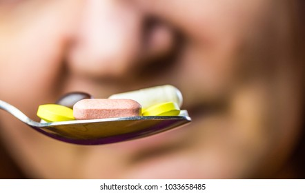 a woman has many pills on her spoon