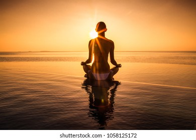 Woman has meditation and Yoga at infinity pool during sunset. Maldives