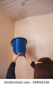 a woman has a problem with leakage. it collects a drop of water leaked from the ceiling.