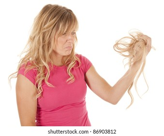 A woman has pulled out a handful of hair and is sad.
