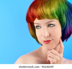 A woman has rainbow colored hair against a blue background. She is thinking and there is very bright colors. Use it for a style or original concept.