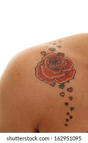 A woman has a rose tattoo on her shoulder.