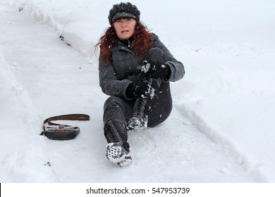 A woman has slipped on the snow and has injured herself