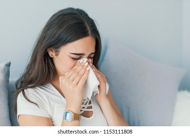 Woman has sneezing. Young woman is having flu and she is sneezing. Sickness, seasonal virus problem concept. Woman being sick having flu sneezing. Fever And Cold. Seasonal influenza and virus.