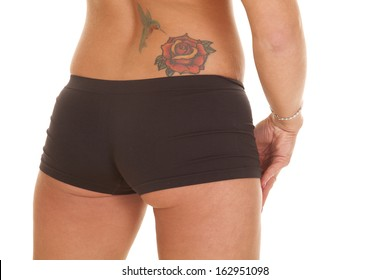 A woman has a tattoo of a rose and a humming bird on her lower back.