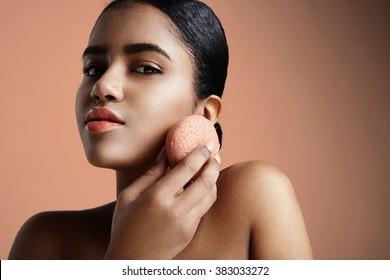 woman has a treatment with a pink konjac facial sponge